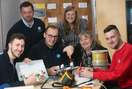 Minister for Skills and Science Julie James tries her hand at being an electrician during her visit to Crimewatch Alarms Ltd and C W Electrical watched by directors Andrew Hutchins and Rachel Meese-Kendall and apprentices (from left) Ewan Maggs, Jacob Slater, Lewis Rowlands.